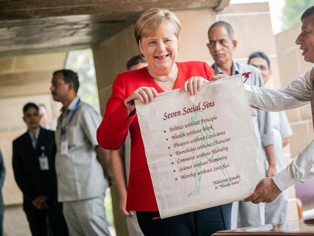 2037811 1 articledetailbig Bundeskanzlerin Angela Merkel bekommt am Denkmal Raj Ghat nach einer Gedenkzeremonie fuer Mahatma Gandhi eine Plakette mit den Seven Social Sins . Fot